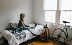 A woman sits in her room while doing work remotely