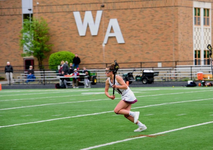 Kendall Donovan cradles the ball as she strides toward the goal. He focus is unwavering.