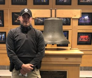 Detective Pavao stands in front of the bell in the bell lobby.