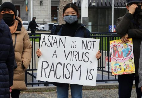 "Woman holds an ""Asian is not a virus, racism is"" sign during an anti-Asian hate protest."