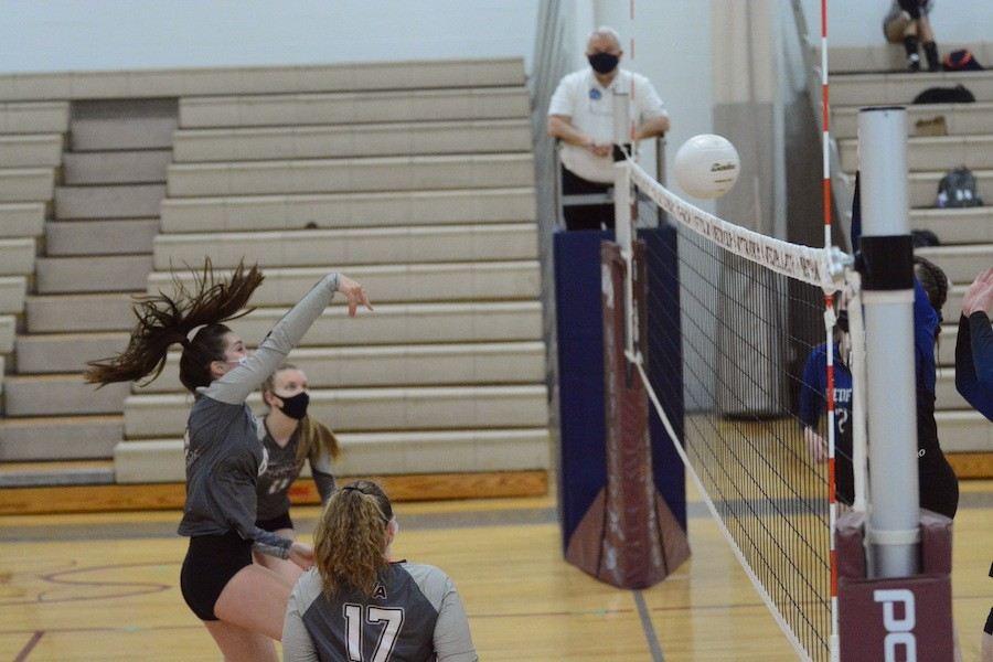 Senior+Ellie+Nolan+spikes+the+ball+over+the+net+while+senior+Haleigh+Millett+%28front%29+senior+captain+Megan+Tierney+%28back%29+look+on.+