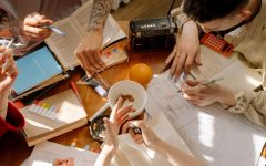 A group of students sit crowded around a table eating and doing work.