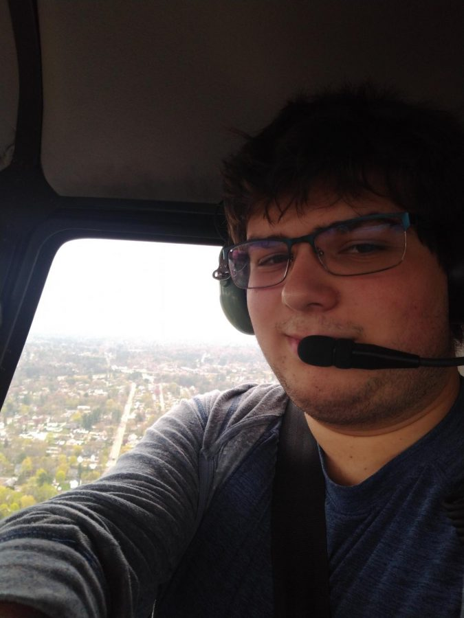 Ben Evangelista in the seat of a helicopter over a city. Evangelista is working as an intern for CR Helicopters as his Capstone Project.