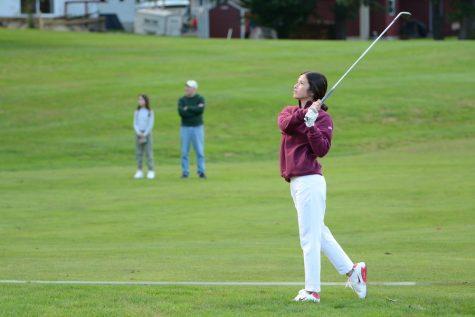Sophomore Alex Kwon watches her shot from the fairway as family members look on in the background.